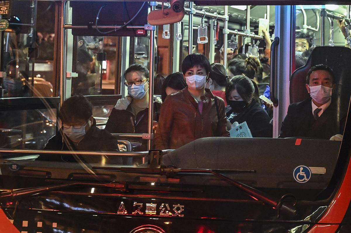 2020年3月,上海街头的一辆公交车上,司机和乘客均佩戴口罩。(图:AFP)