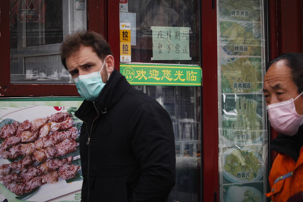 2020年3月1日,新冠疫情期间,一名戴着口罩的外国人走在北京街头。(图:AP)