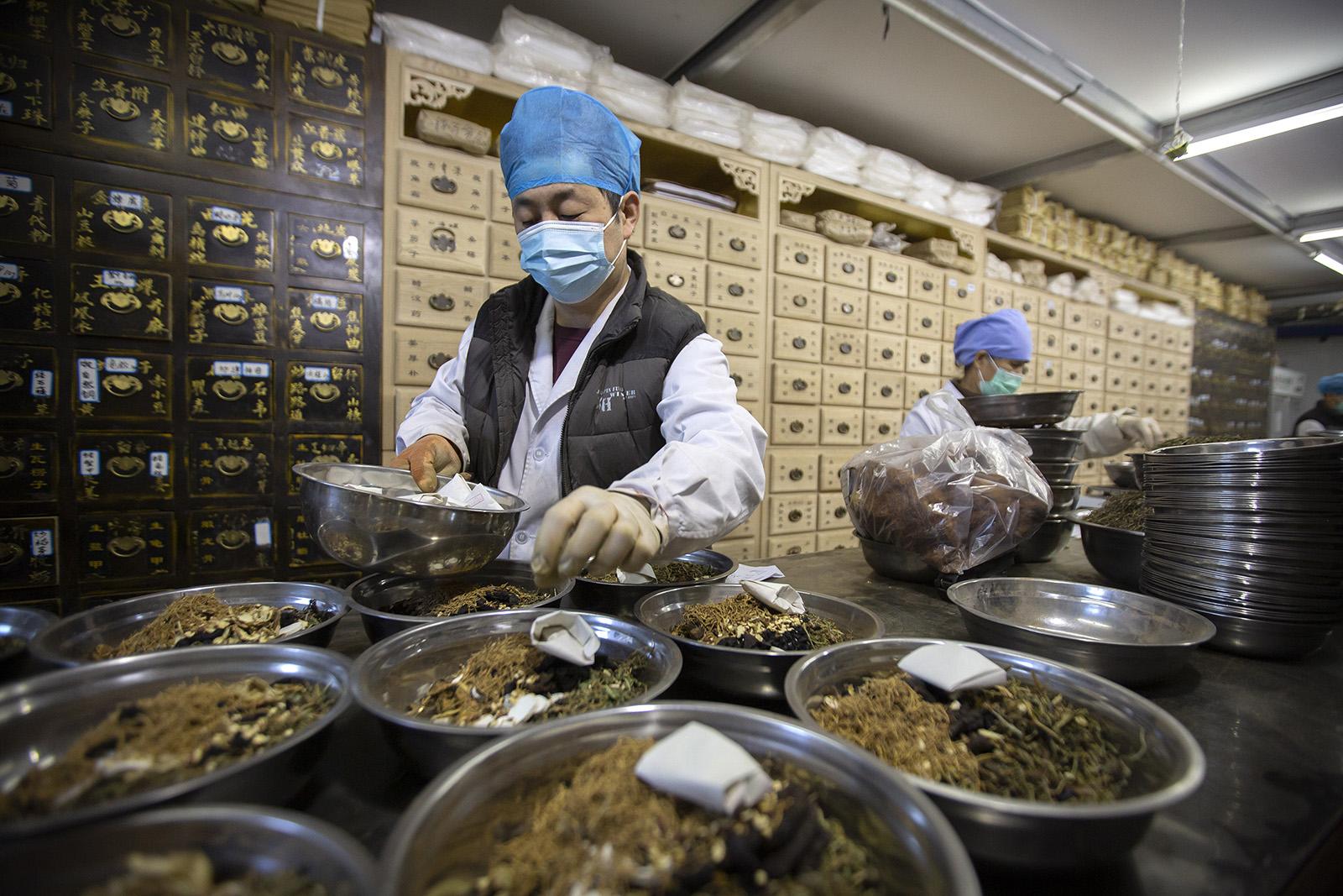 2020年3月13日,新冠疫情期间,北京一家中医诊所的工作人员正在配药。(图:AP)