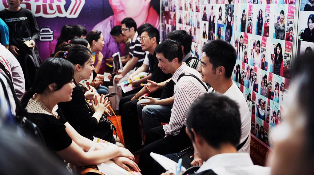 """2012年5月27日,年轻人在上海举行的第二届上海婚姻博览会上""""快速约会""""。(图:AFP / PETER PARKS)"""