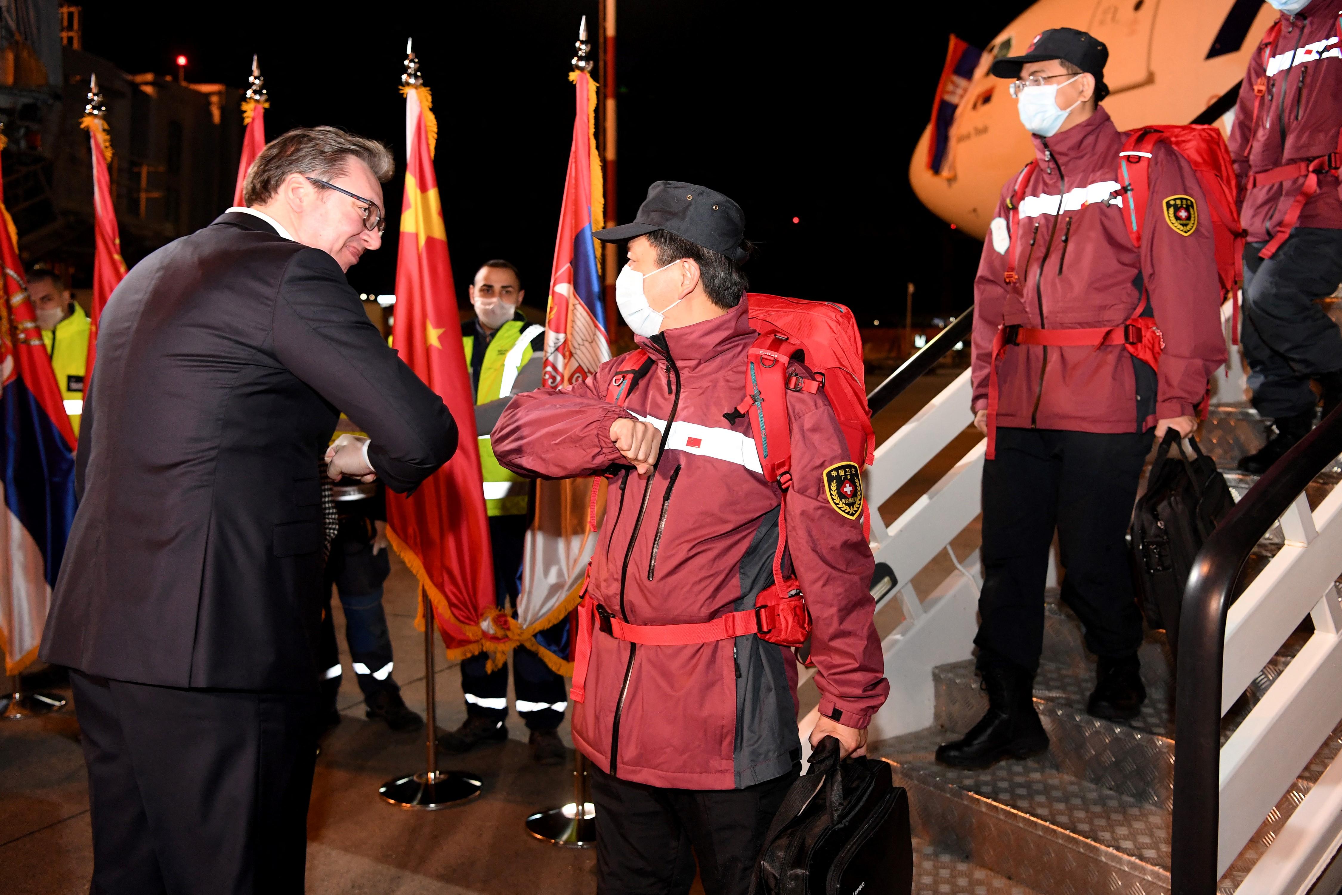 2020年3月21日,塞尔维亚总统武契奇在当地机场与刚刚抵达的中国医疗队成员碰肘表示欢迎。(图:AFP)