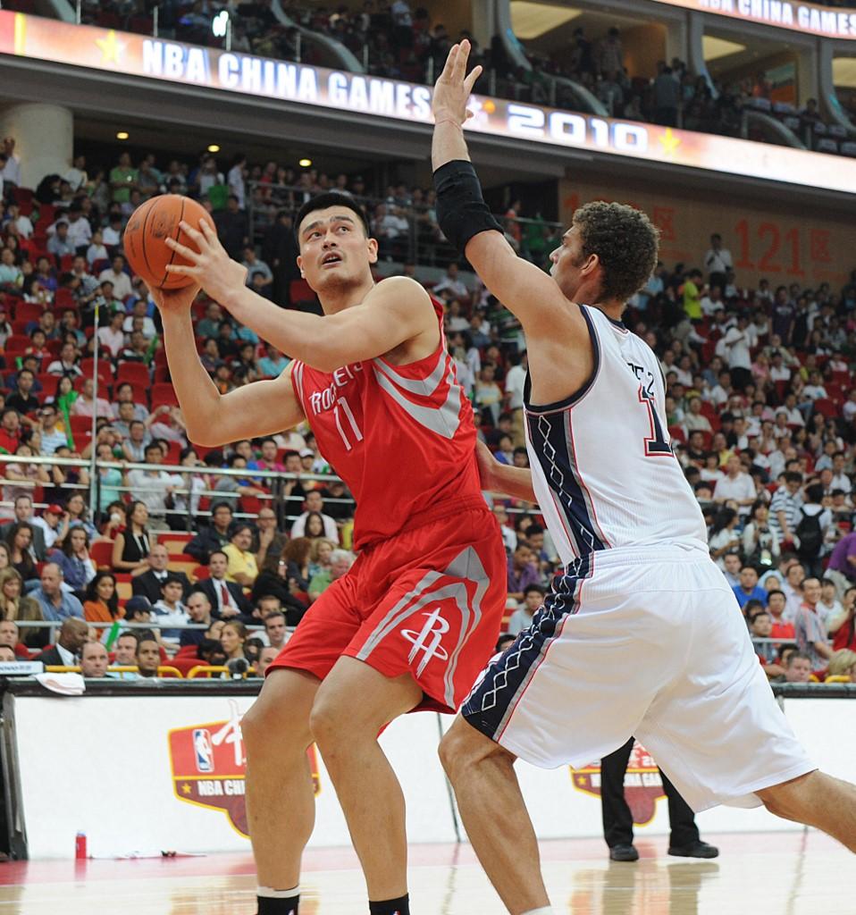 """姚明登陆NBA后曾在中国国内掀起""""篮球热""""。图为2012年10月16日,代表休斯敦火箭队出战NBA中国赛的姚明在比赛中。(图: AFP)"""